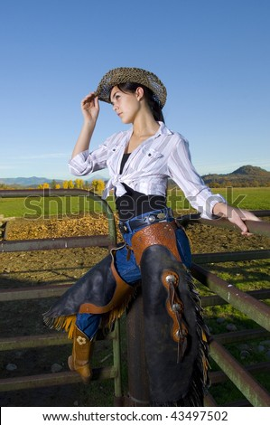 Cowgirl on fence with Fall background - stock photo