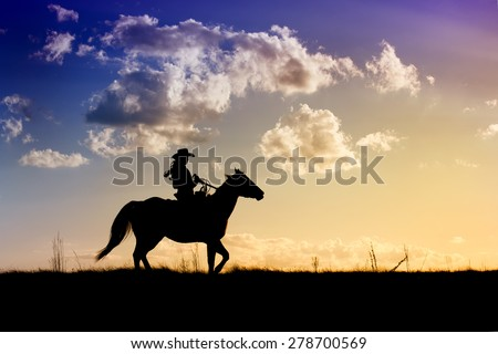 Cowgirl on horse taking an afternoon ride through the pasture at sunset  - stock photo