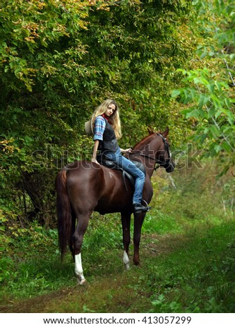 Cowgirl on horseback in woods - stock photo
