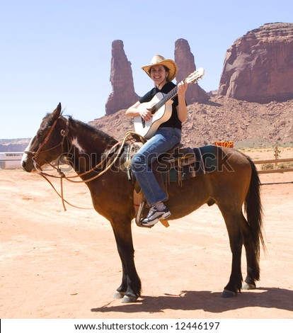 Cowgirl play on guitar. Monument Valley - stock photo