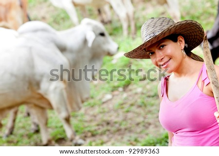 Cowgirl portrait in a farm with cattle at the background - stock photo