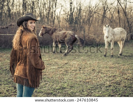 cowgirl posing with horses in the nature - stock photo