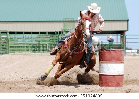 Cowgirl racing her horse between poles during a rodeo. - stock photo