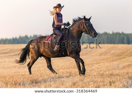 Cowgirl riding a horse at sunset. - stock photo