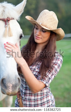 Cowgirl rubbing her horse - stock photo