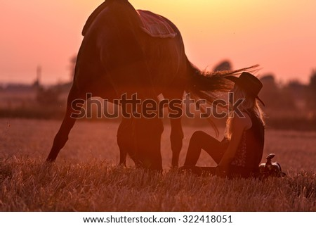 Cowgirl sitting near her grazing horse. - stock photo