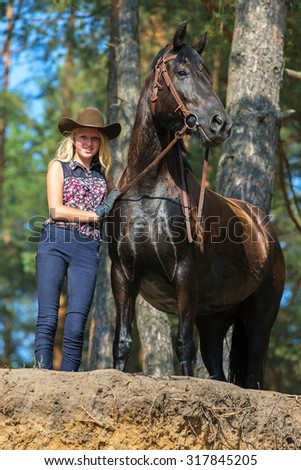 Cowgirl standing near her horse.
