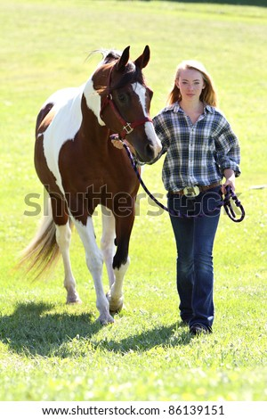 Cowgirl walking her horse - stock photo