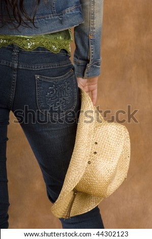 Cowgirl wearing green top with jean jacket and straw hat - stock photo