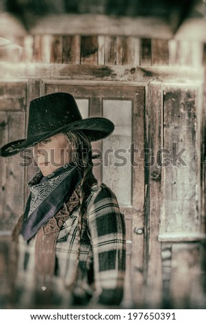 Cowgirl Western Town. Cowgirl with western wooden building door behind her. - stock photo