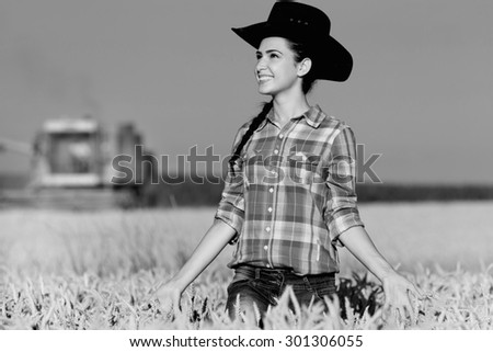 Cowgirl with plaid shirt and hat walking in ripe wheat field during harvest, black and white image - stock photo