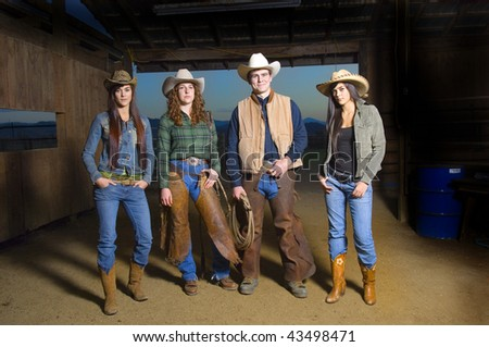 Cowgirls and Cowboy in barn after sunset - stock photo