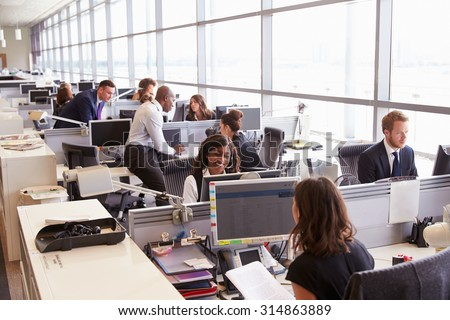 Coworkers at their desks in a busy, open plan office - stock photo