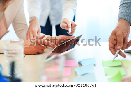 Coworkers discussing the financial status of their business on a digital tablet - stock photo