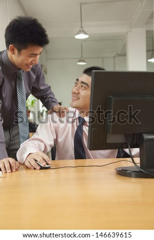 coworkers discussing the project over the computer screen - stock photo