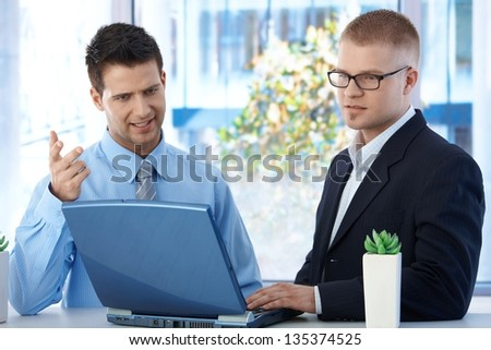 Coworkers discussing work in office, businessmen using laptop computer, concentrating on screen. - stock photo