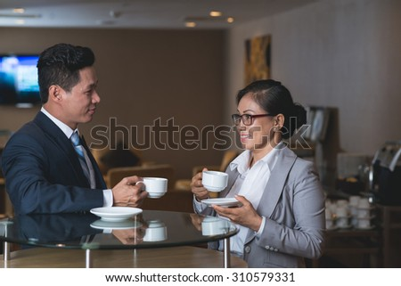 Coworkers drinking tea and discussing business issues in the cafe