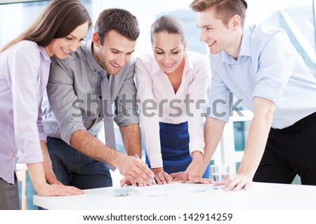 Coworkers leaning over table in office - stock photo