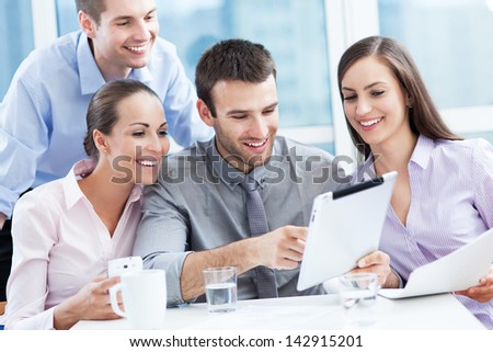 Coworkers looking at digital tablet - stock photo