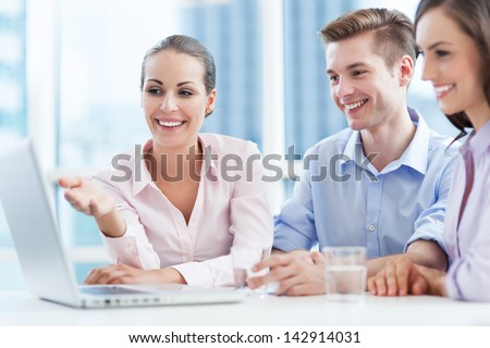 Coworkers looking at laptop - stock photo