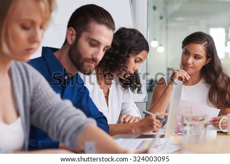 coworkers meeting in boardroom to discuss ideas for company productivity at work - stock photo