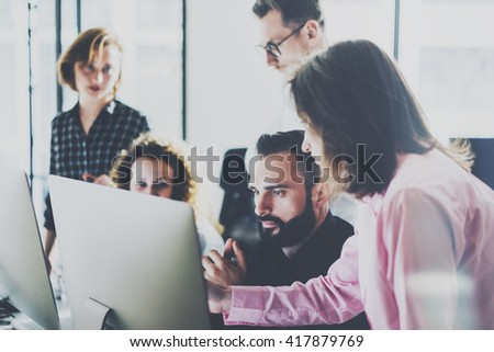 Coworkers photo in modern office.Project manager team work new idea.Young business crew working with startup studio.Desktop computer on table,showing presentation.Blurred,film effect.Horizontal - stock photo