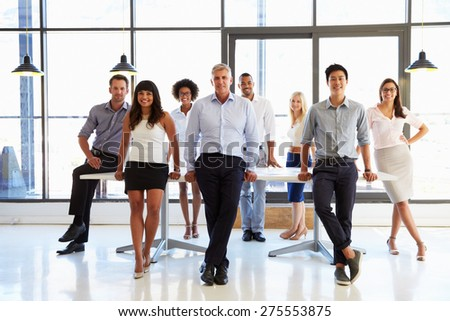 Coworkers posing to camera in meeting room - stock photo