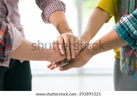 Coworkers stacking hands as a symbol of unity and collaboration