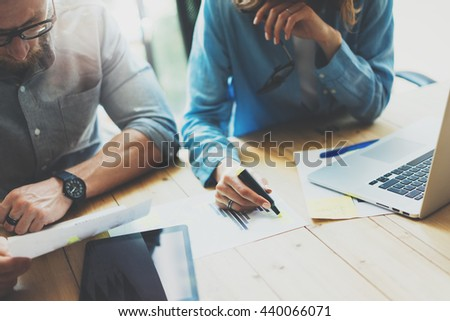 Coworkers team brainstorming process in modern loft.Project manager wearing glasses,woman makes notes marker.Creative business crew working with startup studio.Laptop wood table.Blurred,film effect