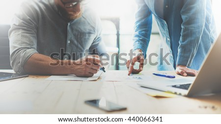 Coworkers team brainstorming process in modern office.Project manager wearing glasses,man makes notes marker.Young business crew working with startup studio.Laptop wood table.Blurred,film effect.Wide - stock photo