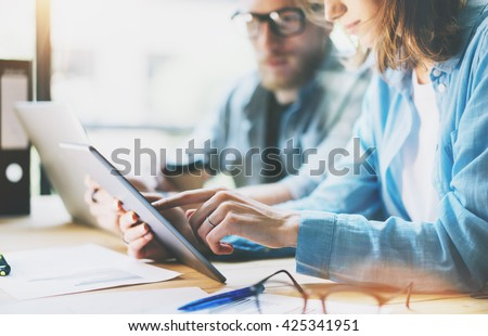 Coworkers work modern studio.Production managers team working new project.Young business crew discussion startup.Laptop computer on wood table,using digital tablet.Blurred,film effect.Horizontal - stock photo