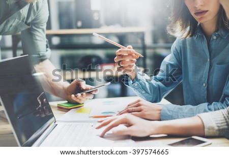 Coworking process. Photo young business crew working with new startup project. Notebook on wood table.  Woman showing screen laptop, man holding smartphone. Blurred background, film effect. Horizontal - stock photo