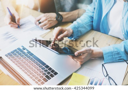 Coworking team work process in modern office.Manager touching screen digital tablet. Young business crew working with startup studio.Laptop table,using electronic devices.Blurred,film effect,flares. - stock photo