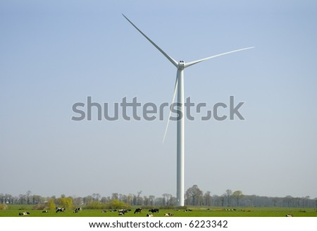 Cows in a meadow pasturing  below an horizontal axis three-bladed wind turbine. - stock photo