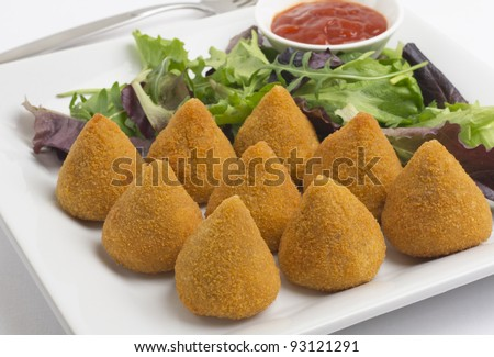 Coxinha de Galinha - Brazilian deep fried chicken snack, popular at local parties. Served with salad and chili sauce. - stock photo