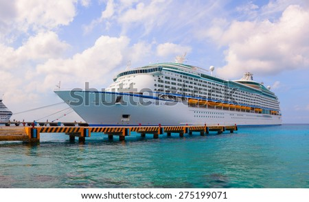 "COZUMEL, MEXICO - FEBRUARY 16, 2012: Large cruise ship ""Voyager of the Seas"" is docked. Over 3,500 guests went out to visit beautiful tropical island. - stock photo"
