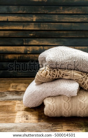 Cozy and soft sweater in a beautiful ornament on wooden background