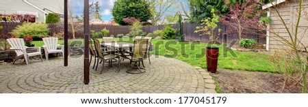 Cozy backyard area with stoned floor, patio table set and white chairs - stock photo