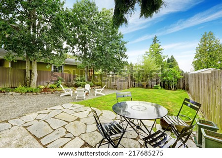Cozy backyard patio area with black and white table sets - stock photo