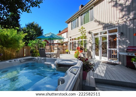 Cozy backyard with patio area and jacuzzi. Walkout deck with flower pots - stock photo