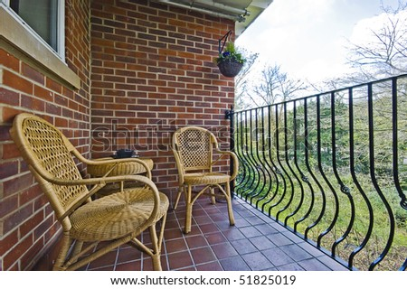 cozy balcony with rattan chair and table over a park - stock photo