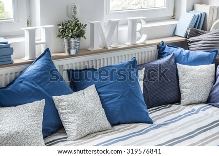 Cozy bed with lots of pillows in children bedroom - stock photo