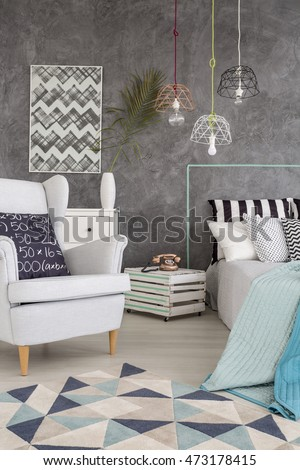 Cozy bedroom in new style with armchair, carpet and decorative wall plaster