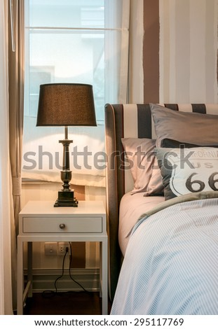 cozy bedroom interior with dark brown pillows and reading lamp on bedside table - stock photo