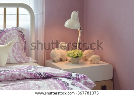 Cozy bedroom interior with decorative sheep dolls and reading lamp on bedside table - stock photo