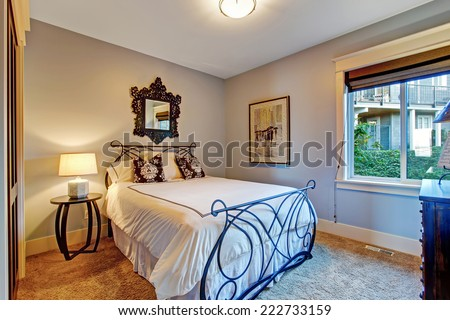Cozy bedroom with soft brown carpet floor and iron frame bed - stock photo