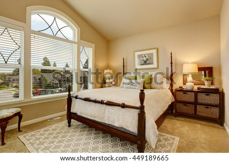 cozy beige bedroom with vaulted ceiling large window and elegant victorian style bed