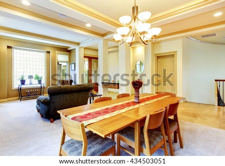 Cozy bright dining room connected with nicely furnished living room. View of entrance door. - stock photo