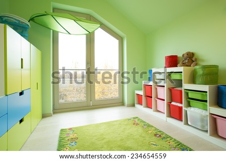 Cozy child's room with green painted walls - stock photo