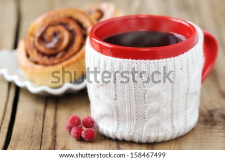 Cozy Christmas setting - a red mug of hot and steamy black coffee with aromatic homemade cinnamon rolls at the background on a rustic wooden kitchen table - stock photo